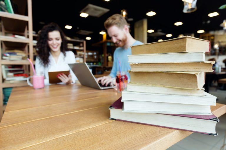 Bøker på et bord med to mennesker i bakgrunnen